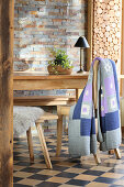 Hand-crocheted blanket on wooden chair next to table