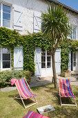 Bunte Liegestühle im Garten vor französischem Landhaus
