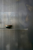 Bowl on simple shelf on black wall