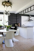 Dining table and designer chairs in front of white open-plan kitchen