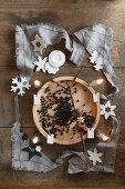 Vier brennende Kerzen und Deko um eine Holzschale als Adventskranz