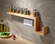 Wall-mounted shelf for spice jars on wooden kitchen wall