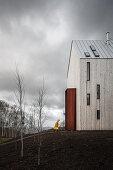 Mann im Regenmantel geht zum modernen Haus auf einem Hügel