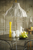 Crockery on table below lamp with knitted lampshade