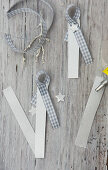 Making festive name tags from strips of paper and gingham ribbon