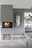 Moderner Kamin mit brennendem Feuer im Raum in Grau