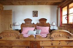 Doppelbett mit rot-weiß karierter Bettwäsche in einer Holzhütte