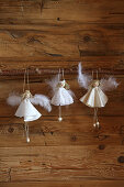 Handmade angels in white dresses on wooden wall