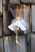 Handmade angel in white dress hung from hinged metal fitting