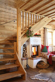 Wooden staircase next to wood-burning stove in log cabin