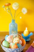 Mit Gouache-Farben bemalte Ostereier vor Kerze und Blumen