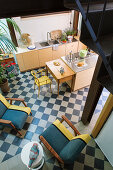 View down into open-plan kitchen with chairs on chequered floor