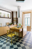Island counter, kitchen table and yellow chair on chequered floor in kitchen with terrace doors
