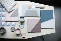 Colour samples on canvases and tins of paint on table