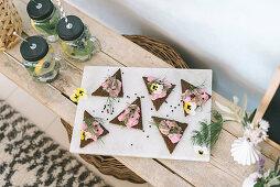 Buffet mit dreieckigen Broten mit rosafarbener Fischcreme