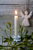 Christmas-tree candle on sprig of mistletoe in front of wooden angel