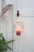 Laterne mit brennender Kerze an einer Holztür