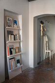 Books presented on ledge shelves leaning against wall in niche