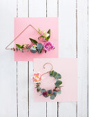 Minimalist floral wreaths on bent wire frames on pink paper