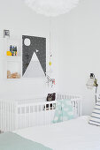 Cot below decorative arrangement on wall of parents's room decorated in white