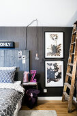 Bed with tall headboard made from reclaimed wood and illustrations on dark wall