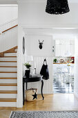 View past black console table in hallway into kitchen-dining room