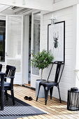 Metal chairs and potted tree below picture of beetle on wall in conservatory