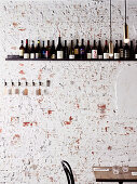 Table in front of rustic stone wall with wine rack (Osteria Ilaria, Melbourne, Australia)