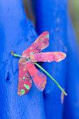 Gebastelte Libellen aus bemalten Ahornsamen auf blauen Ästen
