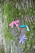 Gebastelte Libellen aus bemalten Ahornsamen an bemostem Baum