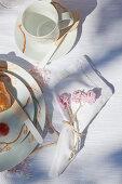 Nostalgisches Tischgedeck mit selbst bemaltem Geschirr und Häkelblüten