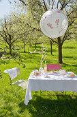 Lampion über gedecktem Tisch unter blühendem Kirschbaum im Garten