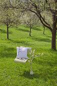 Romantischer Platz unter blühendem Kirschbaum: DIY-Kissen auf Stuhl, daneben umwickelter Ast mit Häkelblüten