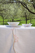 DIY-Tischdecke und Frühstücksgeschirr mit Kirschblütenmotiv auf Tisch unter blühendem Kirschbaum im Garten