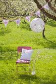 Romantischer Platz unter blühendem Kirschbaum mit Lampion und Wimpelkette: DIY-Kissen auf Stuhl, daneben umwickelter Ast mit Häkelblüten