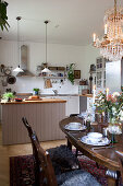 Set dining table next to open-plan kitchen in country-house style