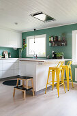 Petrol-blue walls and yellow bar stools in modern kitchen
