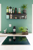 Black shelf mounted on petrol-blue kitchen wall above hob
