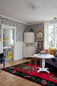White corner cabinet against patterned wallpaper with round white table and sofa on rug in foreground