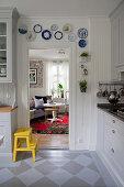 Gelber Tritthocker in Einbauküche mit bemalter Dielenboden, Wandteller an Holzverkleidung über Türrahmen, Blick in Wohnzimmer