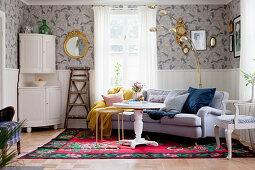 weiße Anrichte in Zimmerecke, runder, weißer Tisch und Sofa auf Teppich im Wohnzimmer