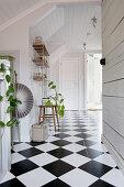 Heller Flur mit weißer Holzverkleidung und Schachbrettmusterboden