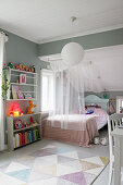 Bed with canopy, book shelves, grey walls and sloping ceiling in girl's bedroom
