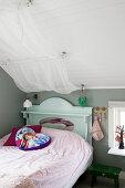 Bett mit Bettvorhang im Mädchenzimmer mit grauer Wand und Dachschräge