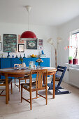 Wooden table and chairs in front of blue sideboard in dining room