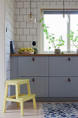 Grey kitchen counter against tiled wall with step stool in foreground