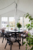 Round table, chairs and houseplants in conservatory