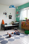 Toys on rug in boy's bedroom with green wall