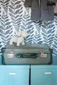 Pale blue storage boxes, suitcase and dog figurine in cupboard with patterned wallpaper on back wall