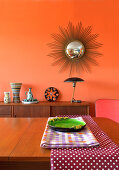 View across dining table to sideboard below sunburst mirror on orange wall